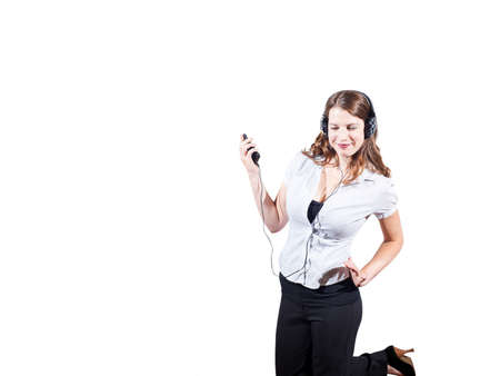 Caucasian female wearing headphones and holding audio device