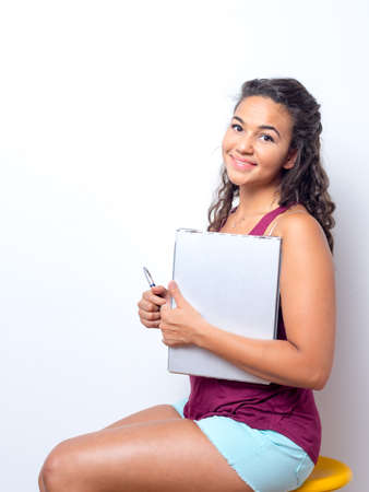 curls: Young lady reviews papers while seated concept. Stock Photo