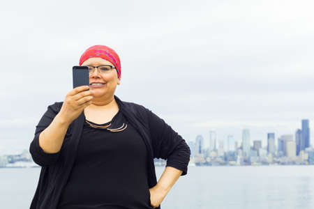 Woman takes in downtown scenery with some selfies.