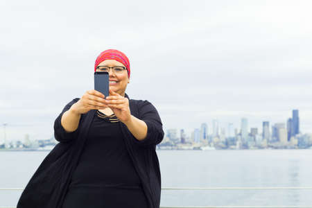 fighting cancer: Woman takes in downtown scenery with some selfies.