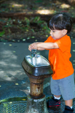 Adorable sweet boy at water fountain