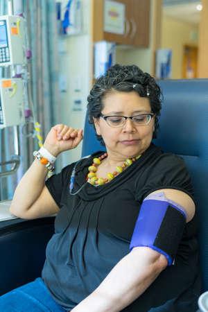 chemo: Hispanic Female Waits Pateintly During Chemo Treatment Stock Photo