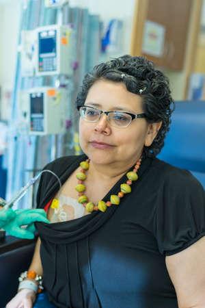waits: Hispanic Female Waits Pateintly During Chemo Treatment Stock Photo