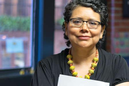 energized: Smiling Woman Holding Documents Stock Photo