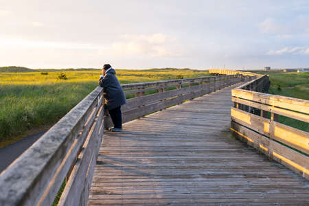 inclement weather: Woman Taking Walk At The Beach Stock Photo