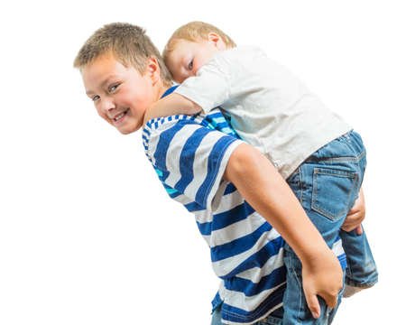well behaved: Big Brother Carries Little Brother On His Back Stock Photo