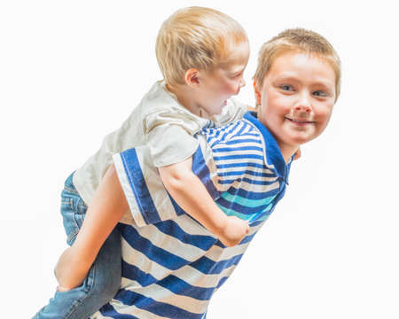 well behaved: Little Boy Has Fun Riding On Older Boys Back Stock Photo