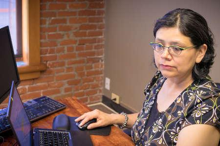 Middle-age woman uses laptop Stok Fotoğraf