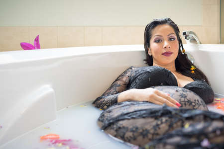 Young pregnant woman in bathtub in final trimester