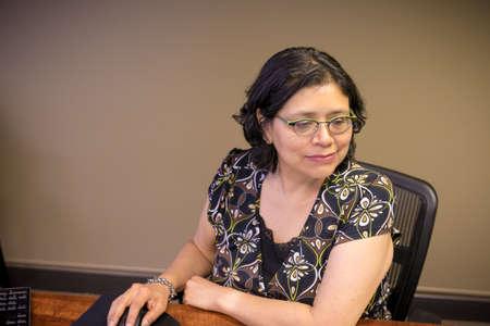 Gen-X Woman Works At Office Desk Archivio Fotografico
