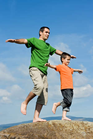 Father and his happy son staying on the stone with lifted legs and balancing