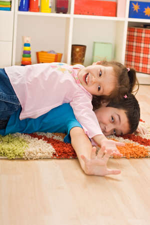 Two happy children playing on the floor