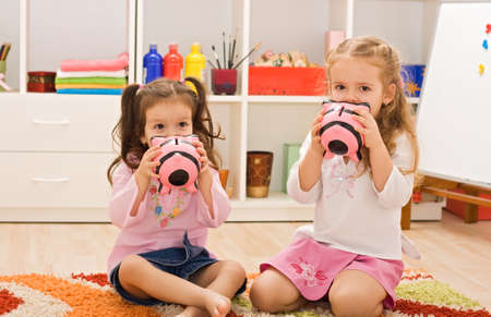 Two little girls kissing the piggybanks and sitting on the floor Stock Photo
