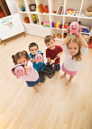 Happy children holding piggybanks