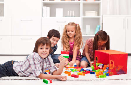 Happy children playing with blocks - focus on the boy  Stock Photo