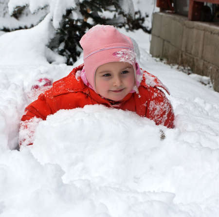 Little adorable girl playing in snow Stock Photo
