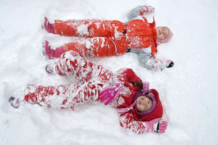 The happy little girls lying in the snow