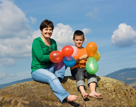 Beautiful woman and her son sitting on the stone with balloons in their hands