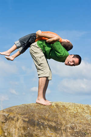 Boy balancing on his fathers back