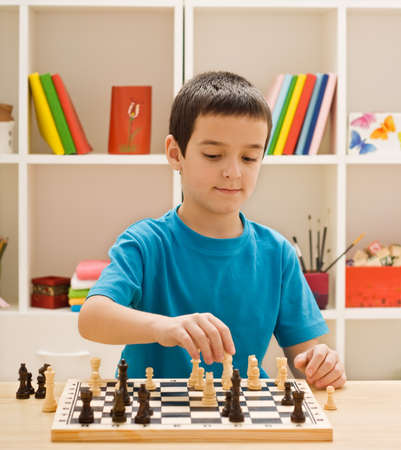 Boy playing chess in the childrens room Stock Photo