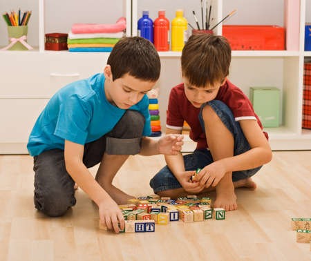 Little boys playing with blocks on the floor