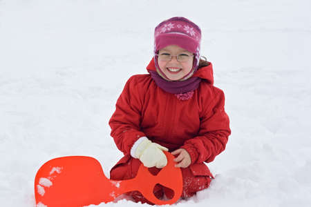Happy little girl resting in the snow Stock Photo