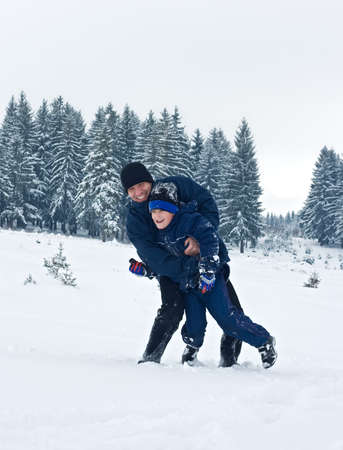 Father and his son playing in the snow on a cloudy day Stock Photo