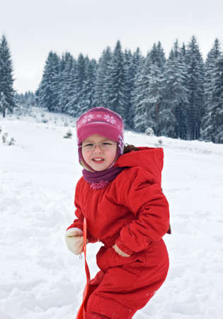Little girl staying in the snow and her hand is cold