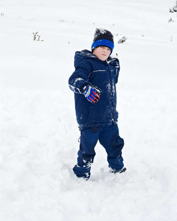 Little boy throwing snowball Stock Photo