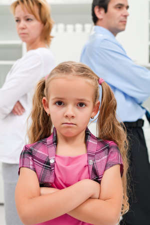 Helpless little girl staying in front of his parents whom are getting divorced