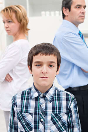 Helpless sad boy staying in front of his parents whom are getting divorced Stock Photo