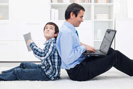 Sad boy with his busy father at home Stock Photo