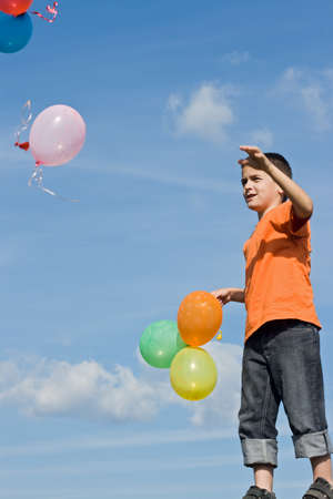 Boy looking at flying balloons photo