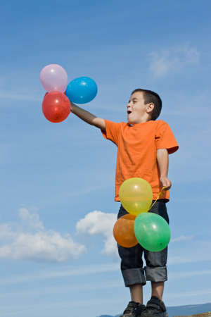 Boy blowing the colored balloons