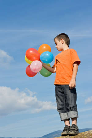 Boy standing on the stone and holding colored balloons