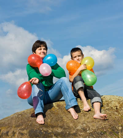 Beautiful woman and her son sitting on the stone with balloons in their hands Stock Photo - 17218726