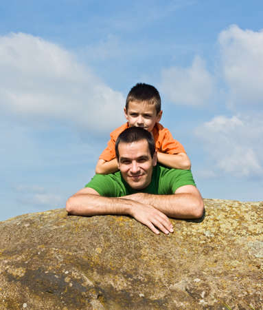 Father and his son leaning on the stone