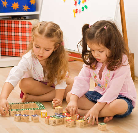 Little girls playing with blocks on the floor Stock Photo
