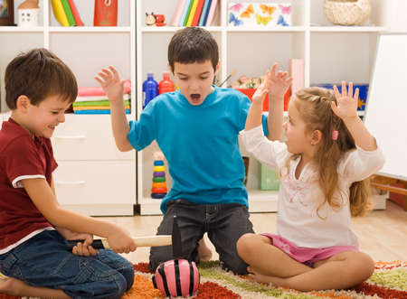 Boy try to break the pink piggybank and the other two children looking frightened Stock Photo