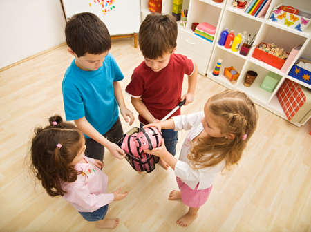 Children gathering piggybanks into a net Stock Photo