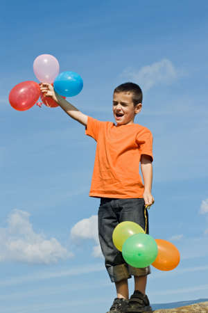 Happy boy standing on the stone and holding colored balloons Stock Photo