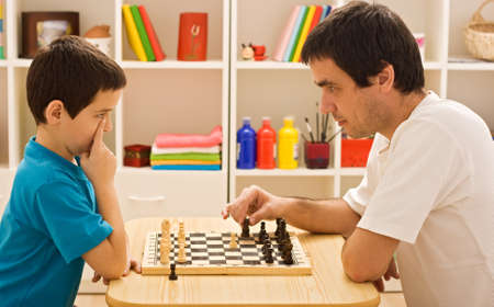 Father showing to his son the first steps of the chess