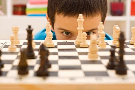 jugando ajedrez: Niño mirando pieza de ajedrez