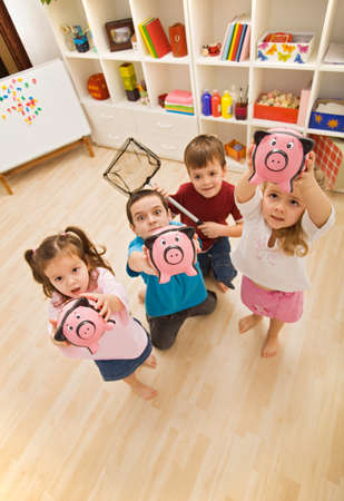 Happy children holding piggy-banks, focus on the piggy-bank photo