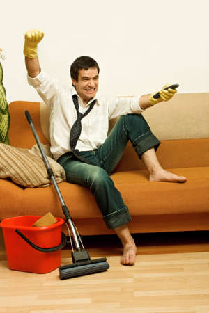 Happy man enjoying a tv show meantime of cleaning the room  Stock Photo