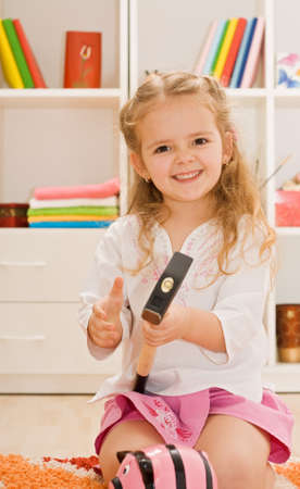 Little happy girl holding a hammer, in front of her is a piggybank photo