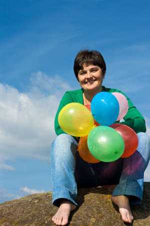 Beautiful woman sitting on the stone with balloons in her hand Stock Photo - 17415968