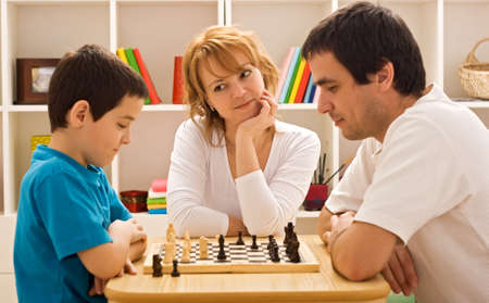 Young beautiful woman smiling to the boy who playing chess with his father, focus on the woman