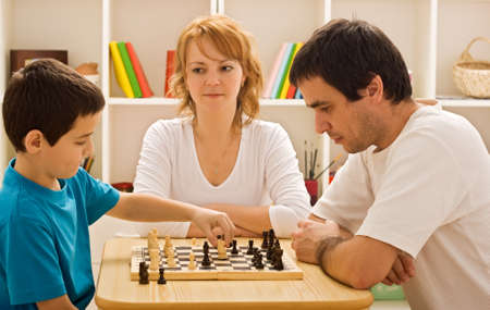 Father and his son playing chess meantime the young beautiful woman smiling, focus on the man photo