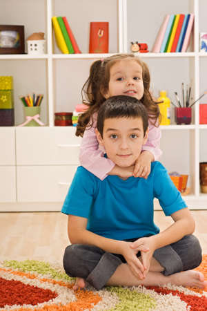 Little girl embracing her brother Stock Photo